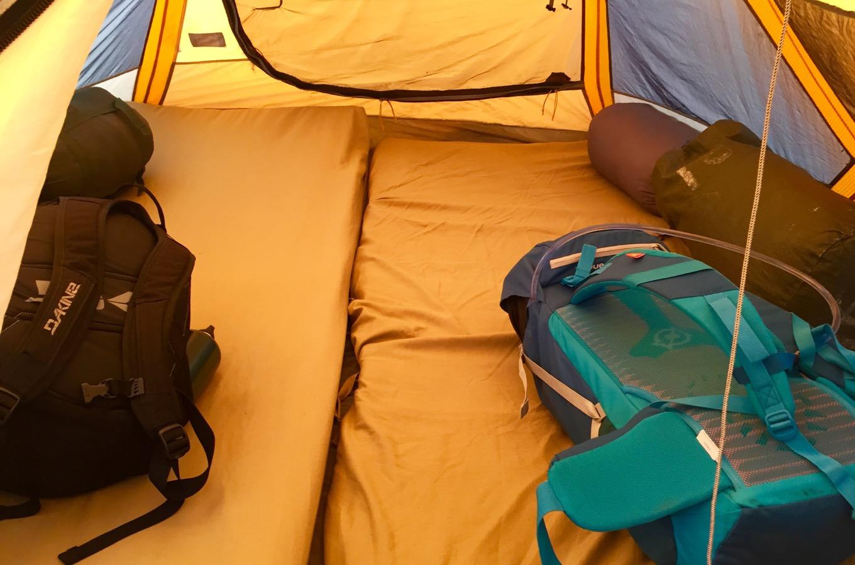 Tente avec des matelas et des sacs à dos
