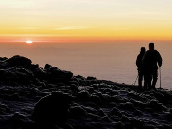 Hiker on the summit of Kilimanjaro at the time of sunrise