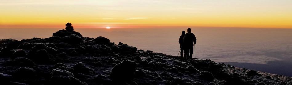 Wanderer am Gipfel des Kilimandscharos zum Zeitpunkt des Sonnenaufgangs