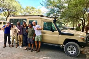 German tour group in front of a safari car in Tanzania