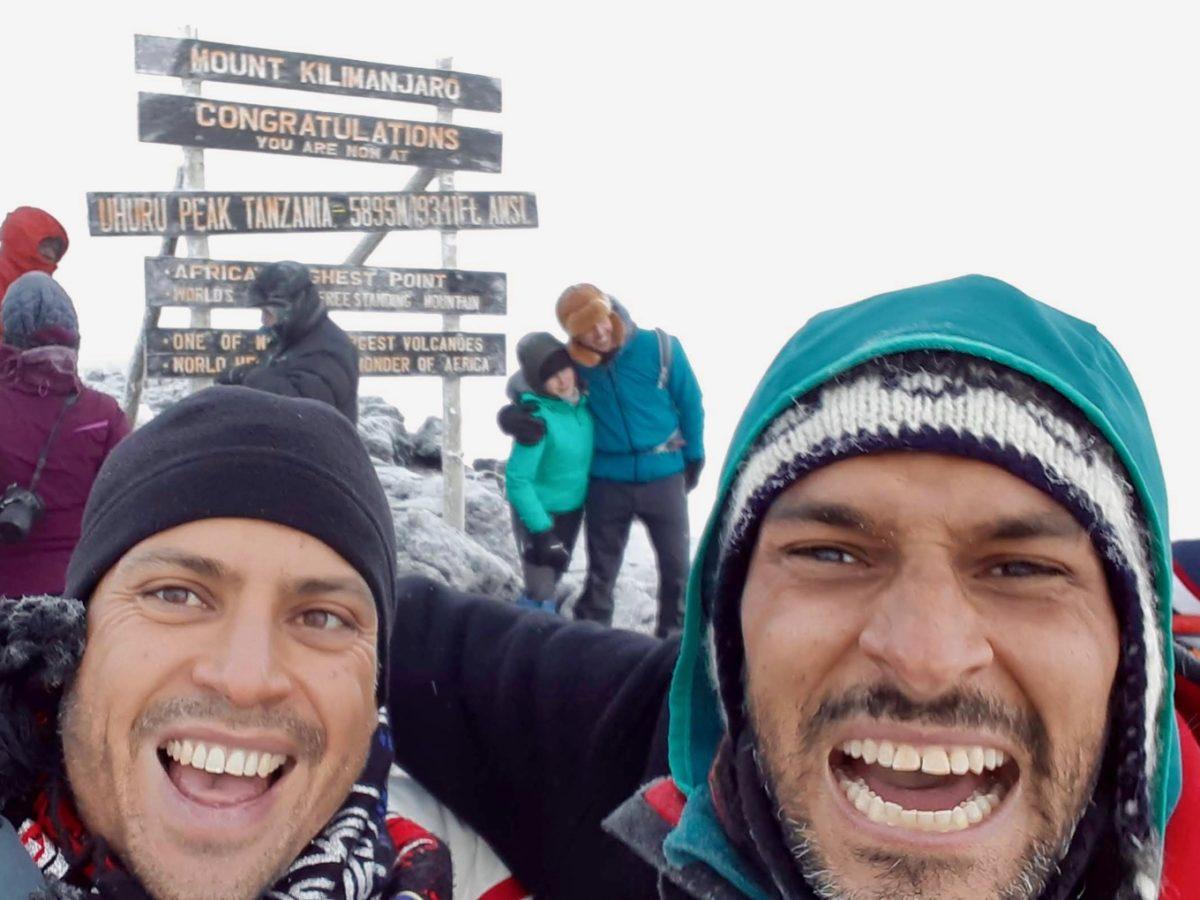 Zwei Bergsteiger vor dem Gipfelschild des Kilimandscharos
