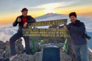 Deux alpinistes se tiennent devant l'enseigne du sommet du Mont Meru, le pic socialiste.