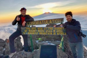 Two mountaineers stand in front of the summit sign of Mount Meru, the Socialist Peak.