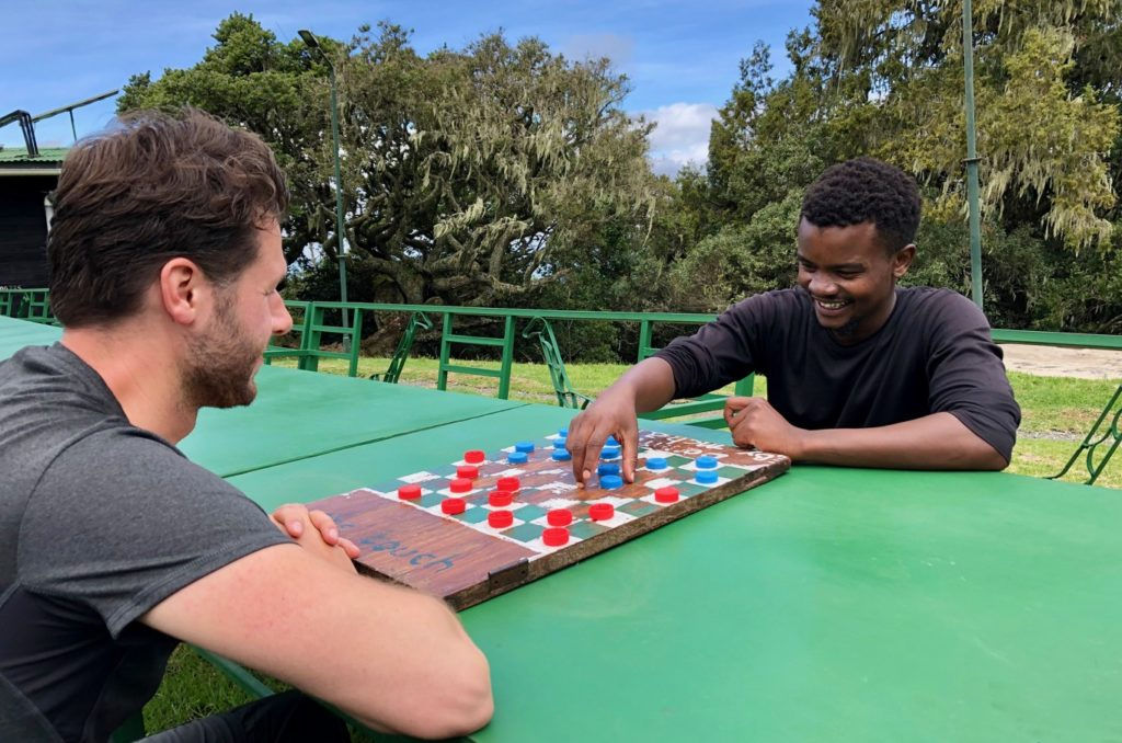 Mountaineers at Mount Meru play checkers at camp