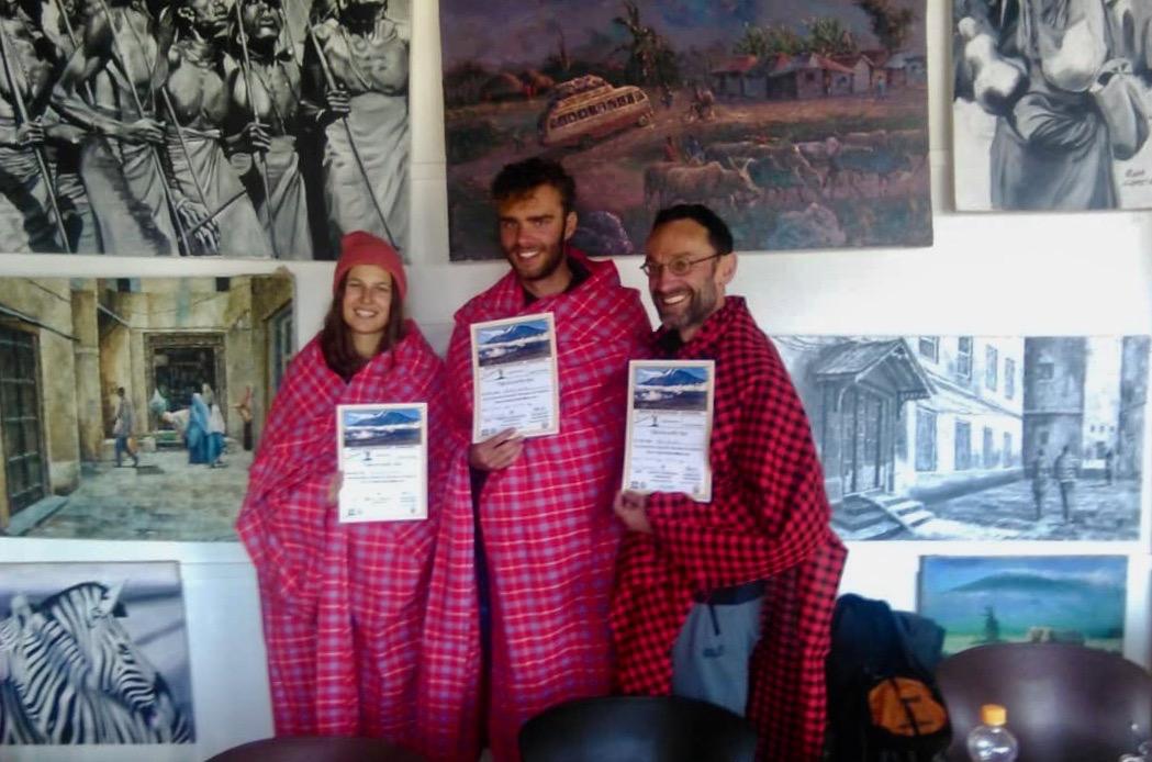 Trois alpinistes après une ascension réussie du Kilimandjaro